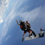 Carl Osburn jumping out of a plane with instructor