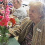 Mary, a resident, admiring flower arrangement