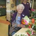 Smiling Watermark resident with flower bouquet from garden