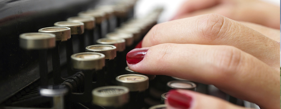 Contact us - Hands typing on typewriter