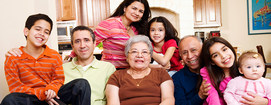Multi-generational family of eight smiling, ready to communicate about senior housing